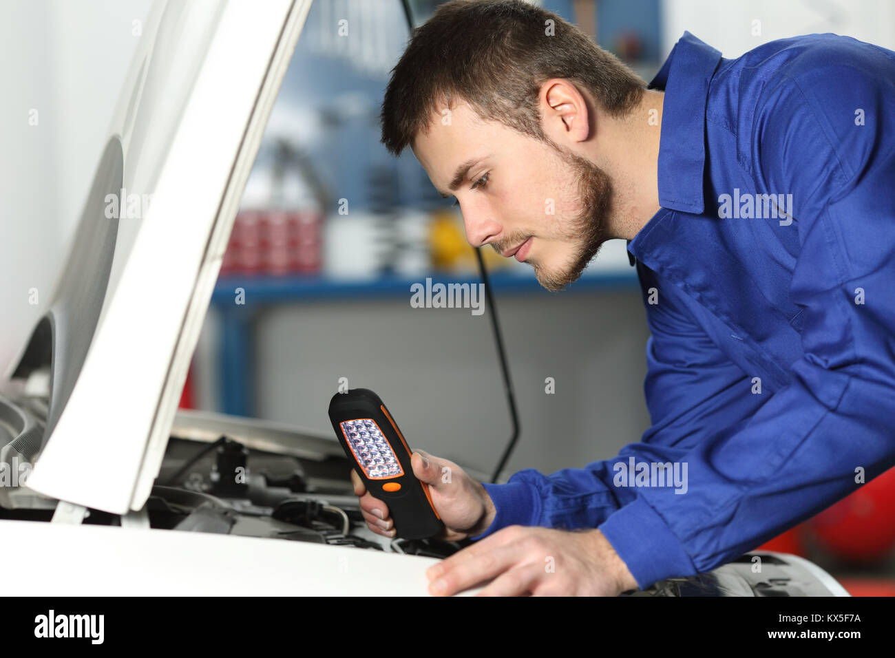 Side view of a car mechanic checking engine for failures in a mechanical workshop - Stock Image