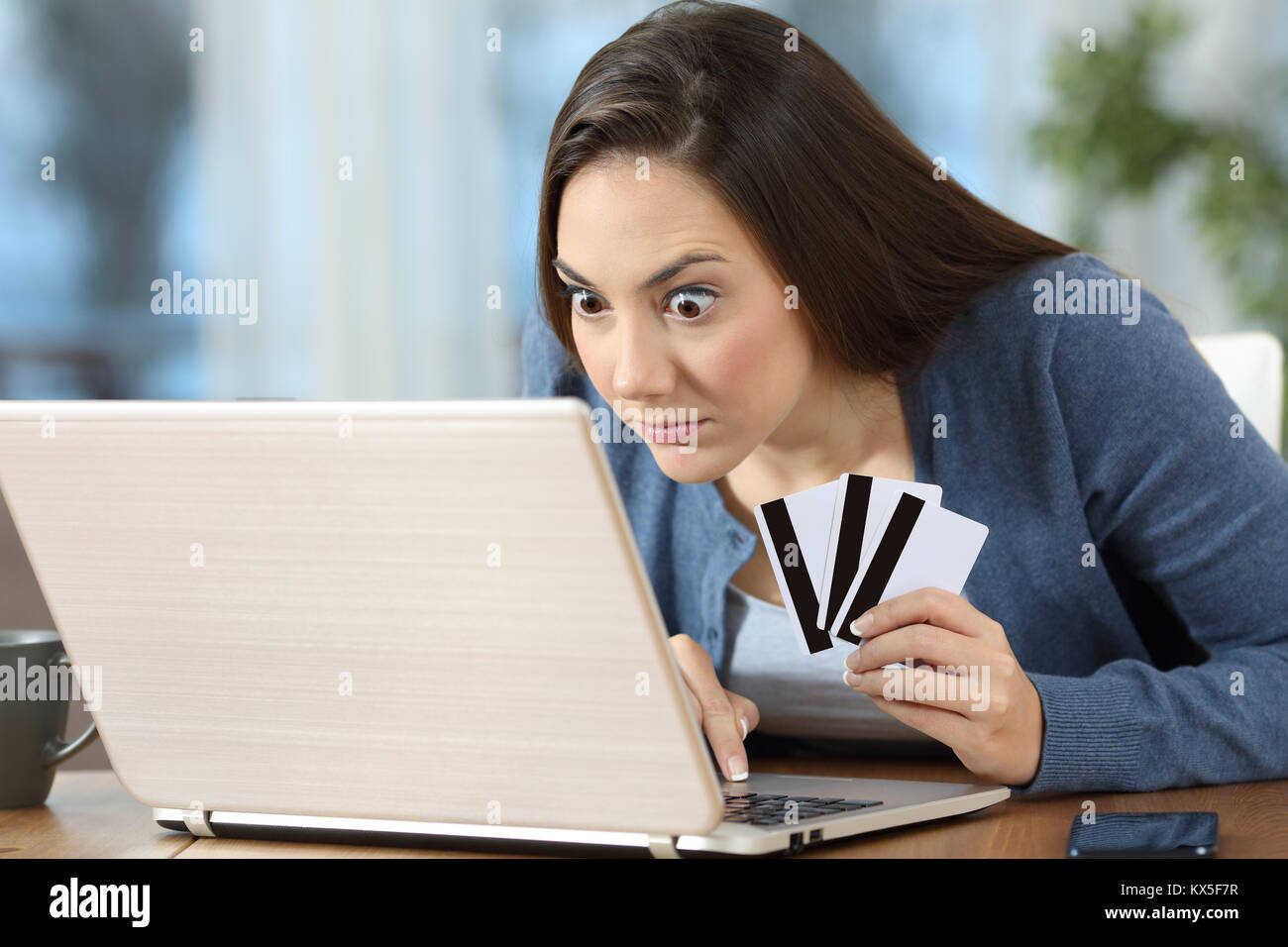 Obsessed compulsive on line shopper or gambler checking results in a laptop at home - Stock Image