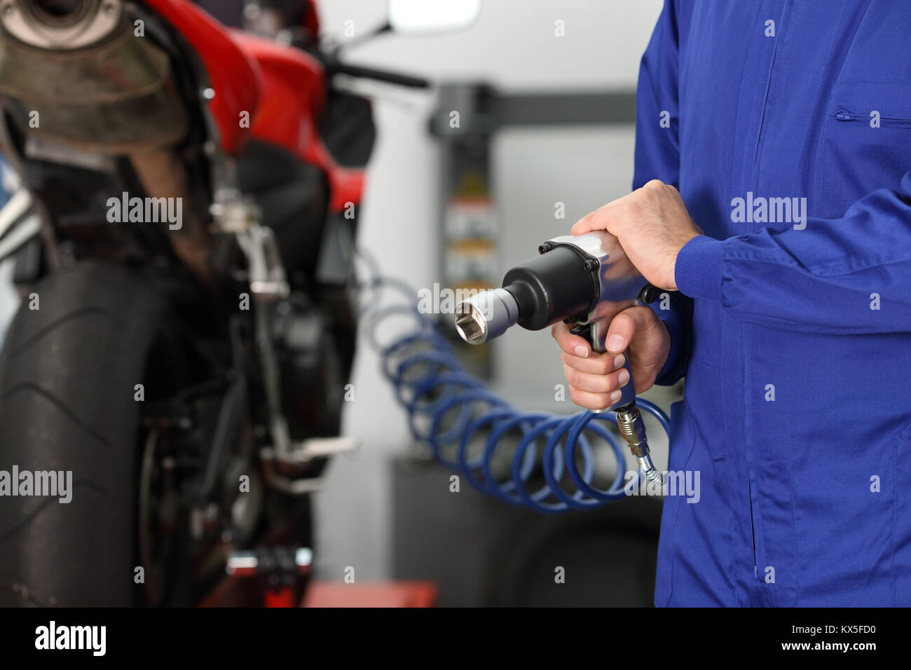 Close up of a motorcycle mechanic hand holding a pneumatic gun in a mechanical workshop - Stock Image