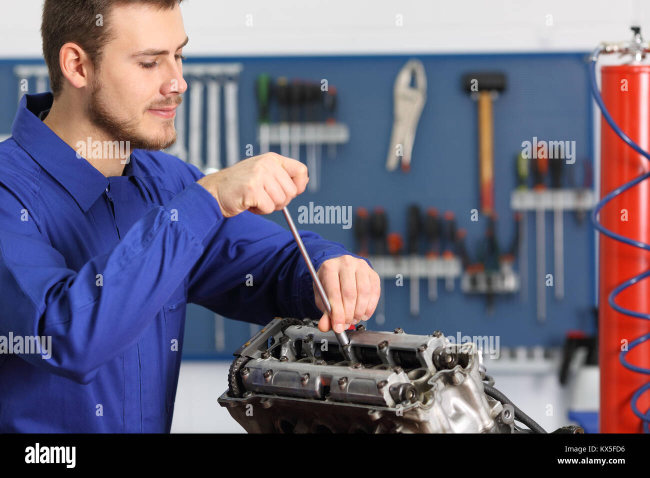 Satisfied mechanic repairing a motorbike engine in a mechanical workshop - Stock Image