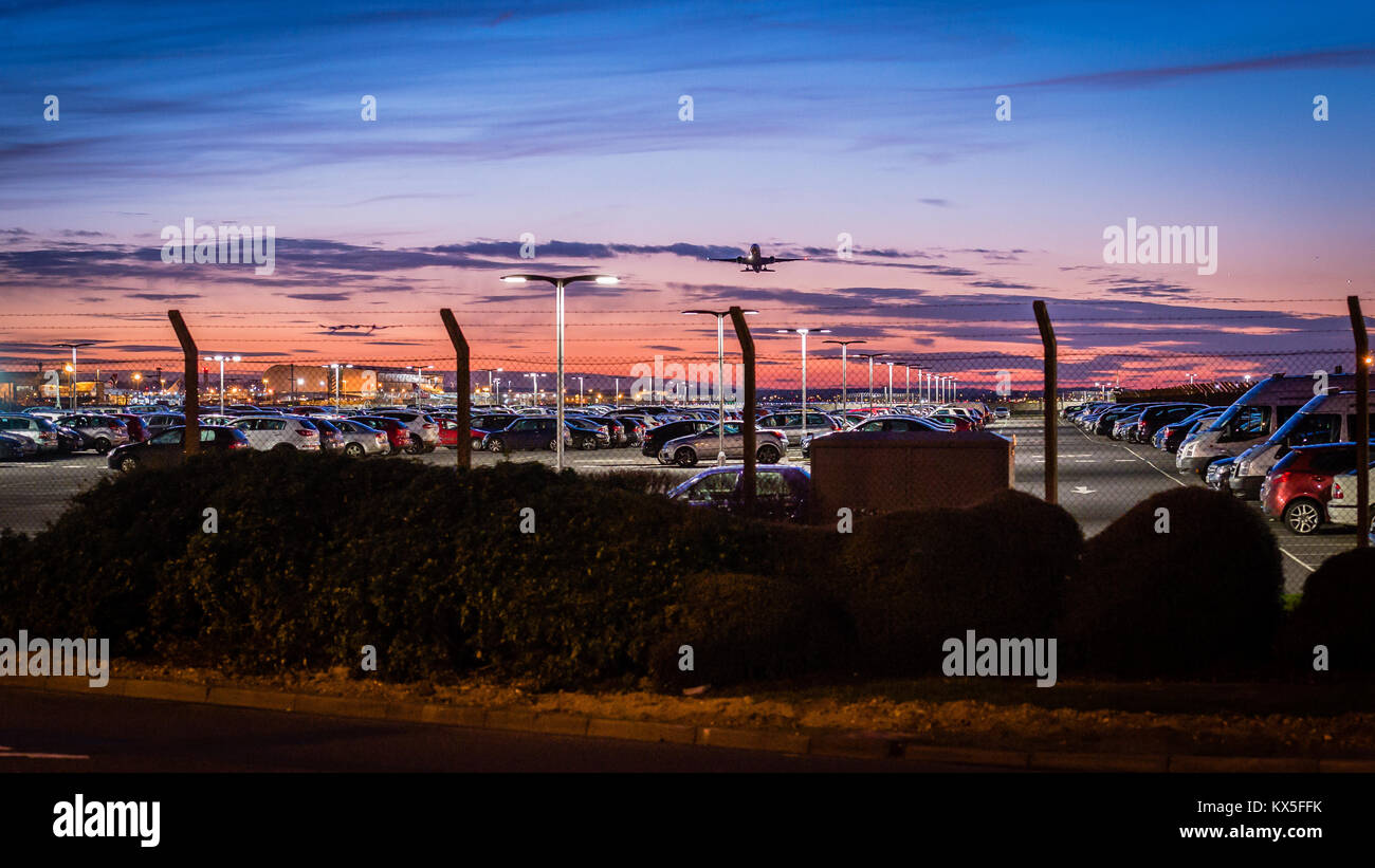 An aircraft takes off from London Heathrow Airport, departing over the airport secure car parking into a beautiful - Stock Image