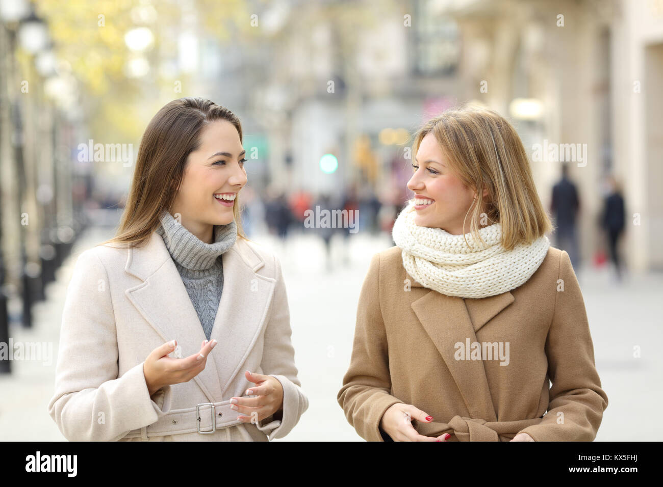 Front view portrait of two women friends wearing coats talking and walking on the street - Stock Image