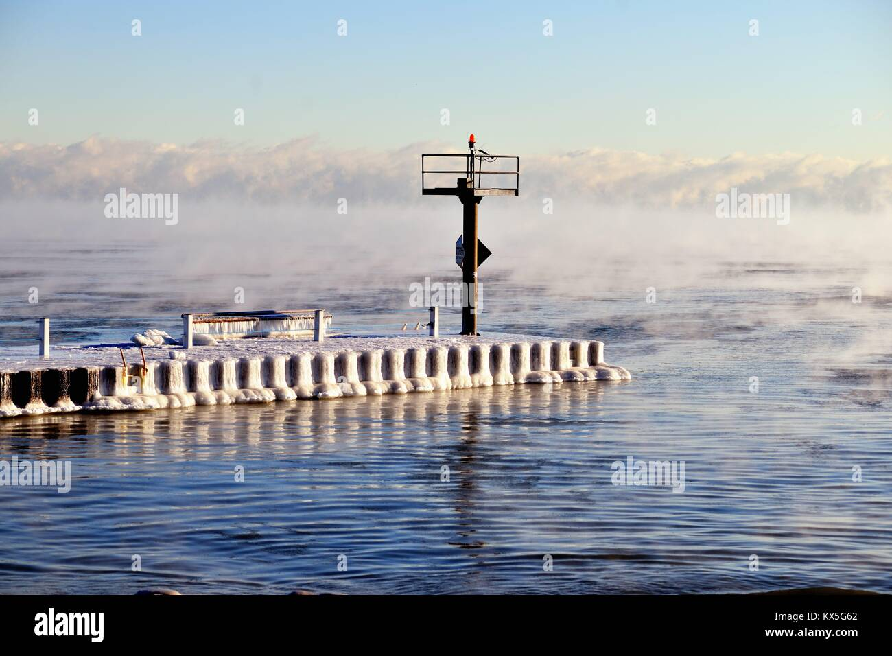 Ice forms on a breakwater as vapor rises from the Lake Michigan waters as ice forms in Chicago's 31st Street - Stock Image