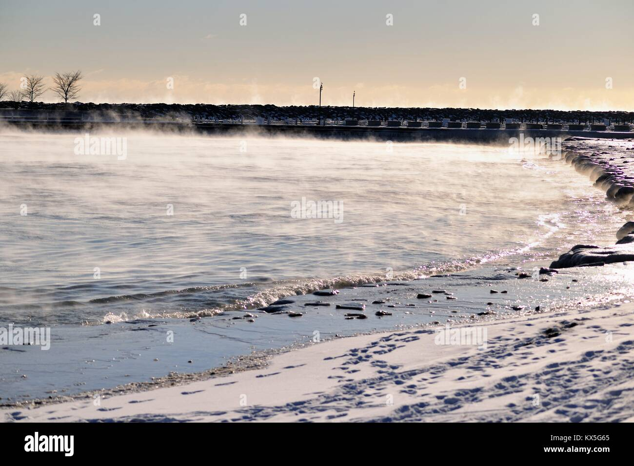 Vapor rises from still flowing water as turns to Ice on Lake Michigan waters in Chicago's 31st Street Harbor. - Stock Image