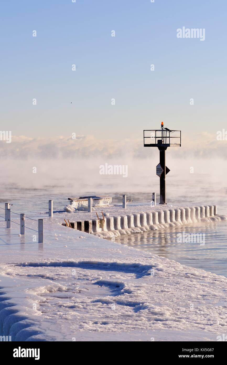 Ice coats on a breakwater as vapor rises from the Lake Michigan waters as ice forms in Chicago's 31st Street - Stock Image