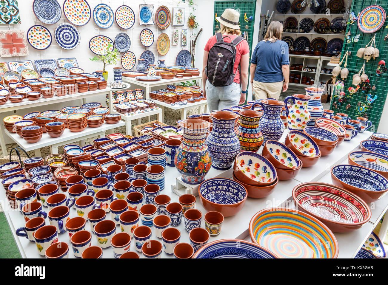Lisbon Portugal Castelo quarter shopping store souvenir clay pottery plates platters vases mugs hand painted terracotta - Stock Image