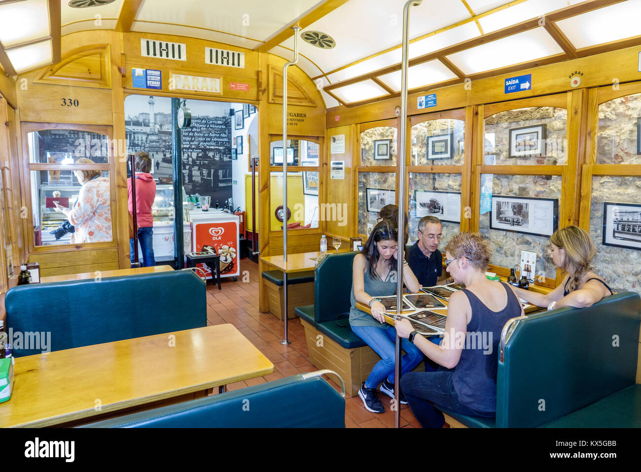 Lisbon Portugal Alfama historic neighborhood 28 Cafe restaurant tram car dining booth man woman Portuguese Europe - Stock Image