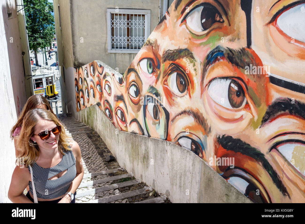 Lisbon Portugal Alfama historic neighborhood Beco do Maldonado stairs alley graffiti street art woman eyeballs eyes - Stock Image