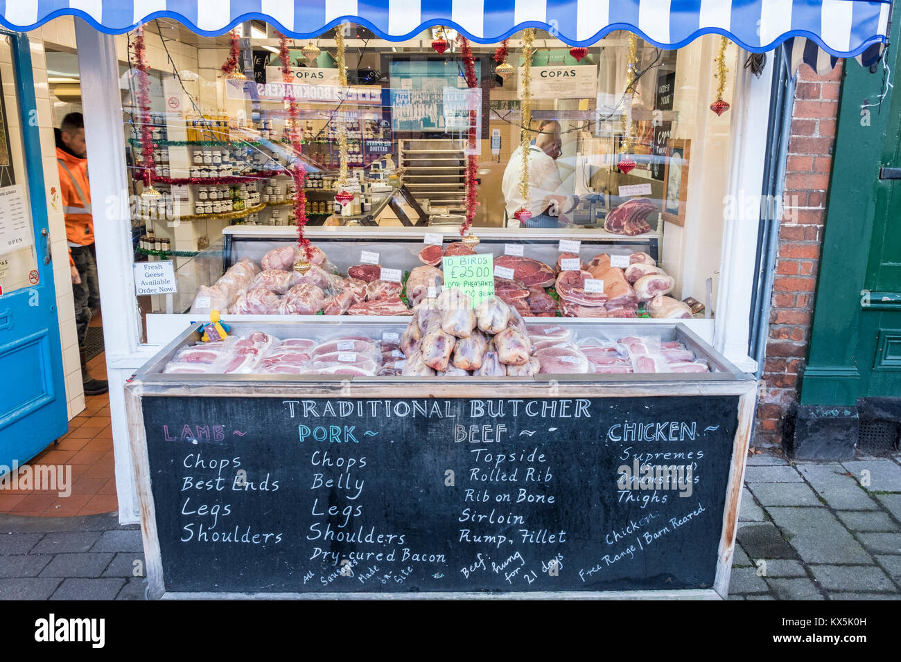 Traditional butcher's shop window display with fresh meat for sale on display. Hartley Wintney, Hart, Hampshire, - Stock Image