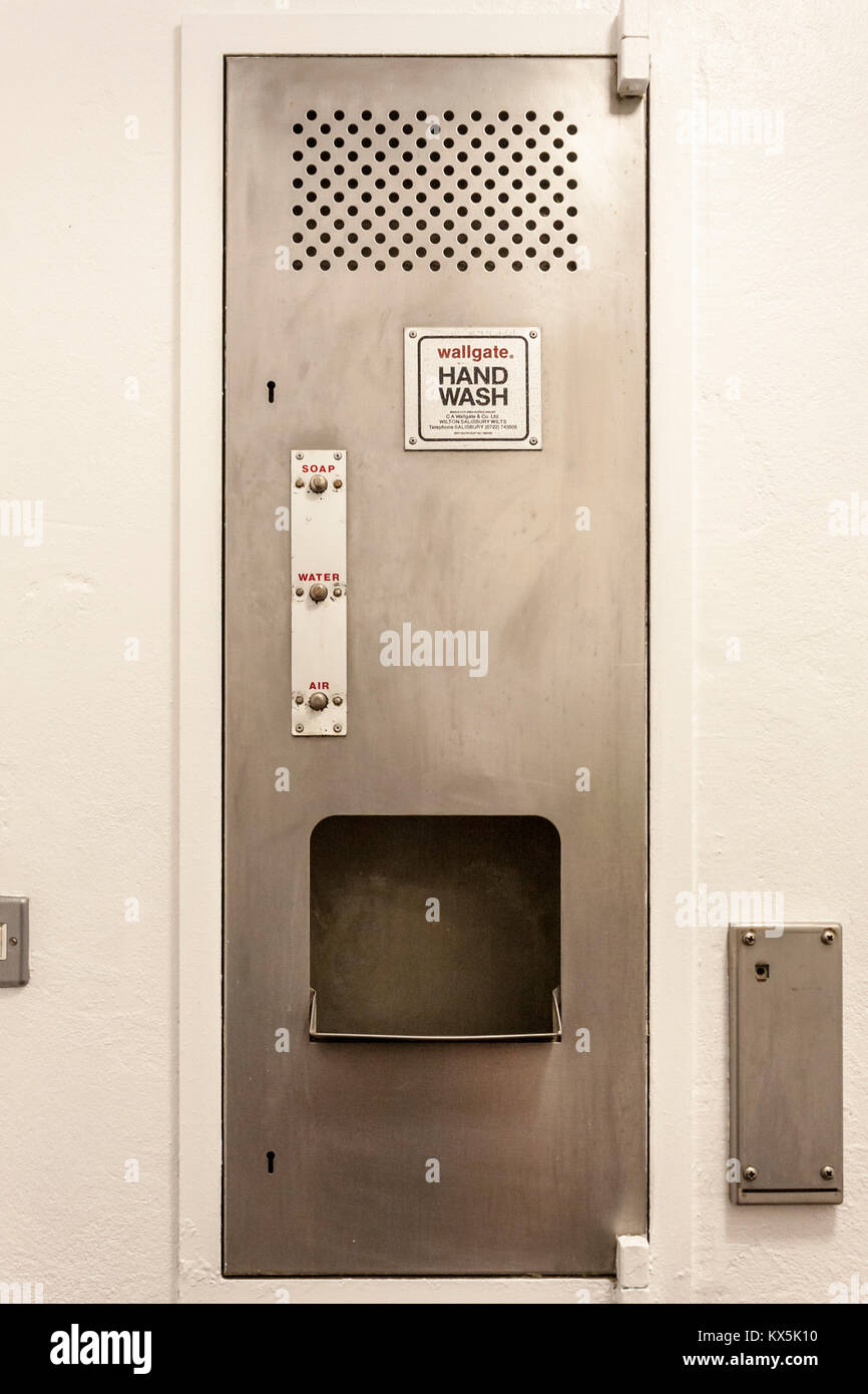 Wall mounted stainless steel hand wash dryer unit in a commercial washroom. - Stock Image