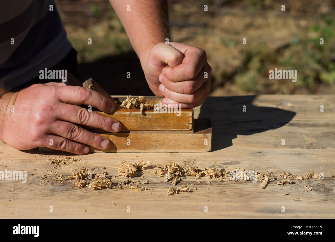Hands of a carpenter planed wood planes, work on nature - Stock Image