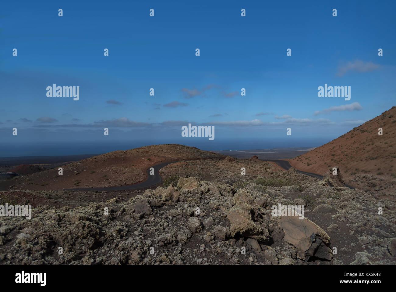 Der Nationalpark Timanfaya auf Lanzarote mit den Feuerbergen und den Blick zum Meer - Stock Image