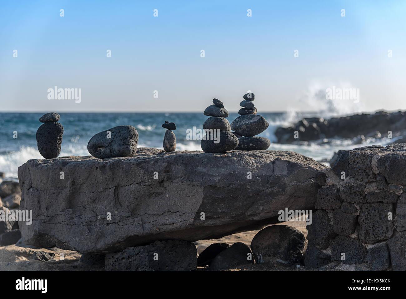 Steinskulpturen aus aufgeschichteten Lavagestein an der Küste von Costa Teguise auf Lanzarote - Stock Image