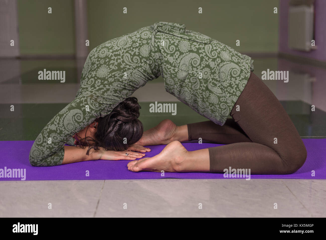 Lady shows yoga positions in fitness class - Stock Image
