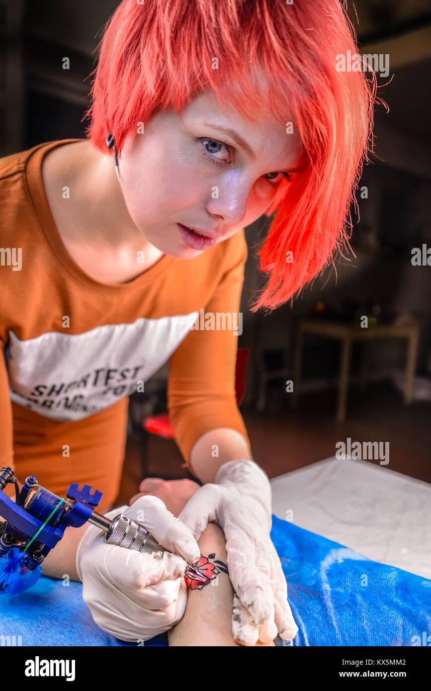 Tattoo master working on professional tattoo machine gun in tattoo studio - Stock Image
