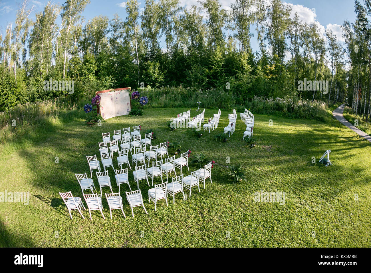 Beautiful setting for outdoors wedding ceremony waiting for bride and groom and guests. White chairs decorated with - Stock Image