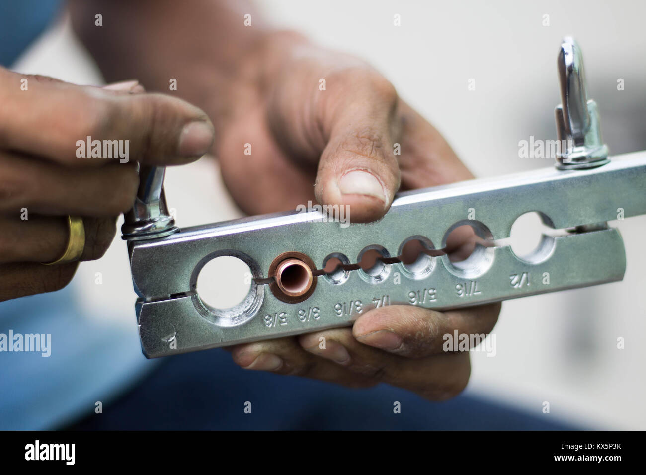 The hand of technician with tube flaring tool in air condition service - Stock Image