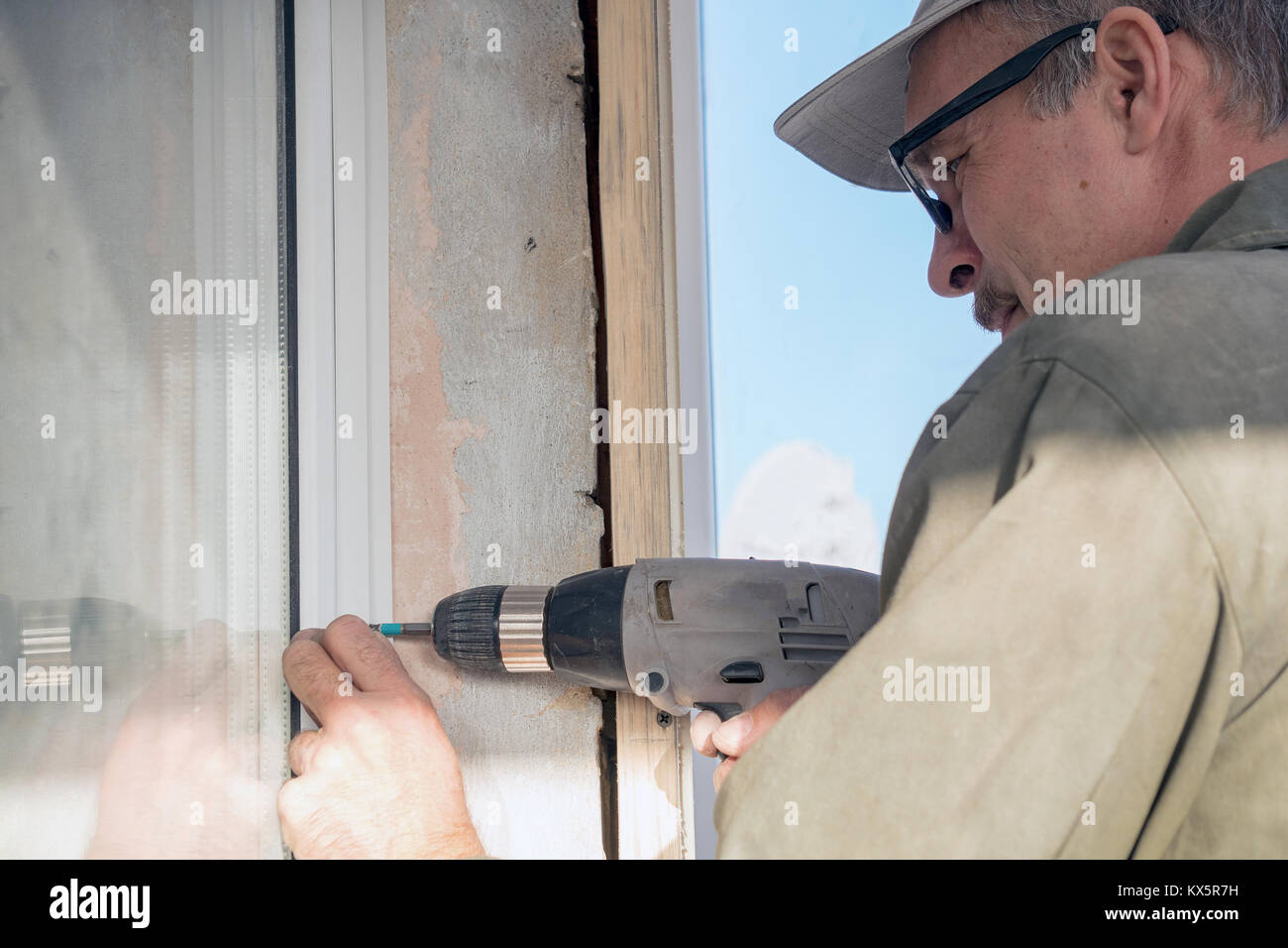 Carpenter in glasses with a drill - Stock Image