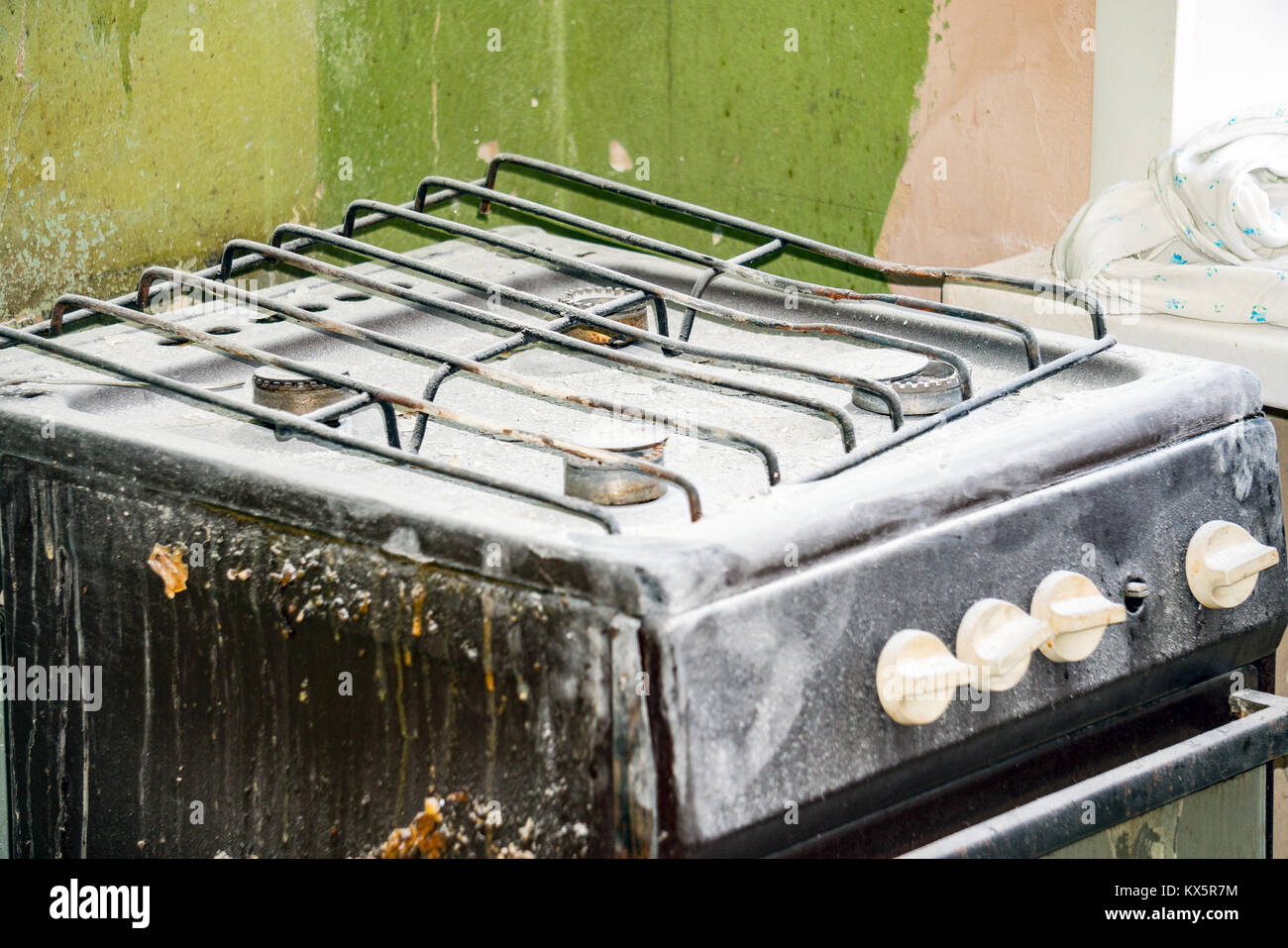 Old dirty gas stove in an abandoned state - Stock Image