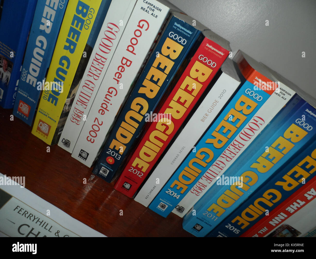 A selection of Camra Good Beer Guide books an a shelf in an English pub in Durham, England. - Stock Image