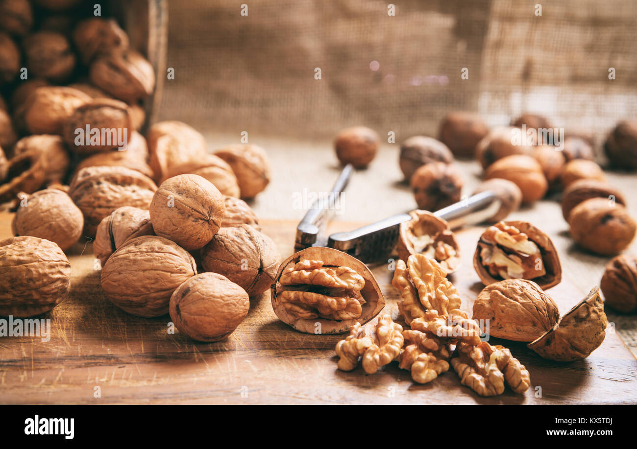 Walnuts and an old nutcracker on a table - Stock Image