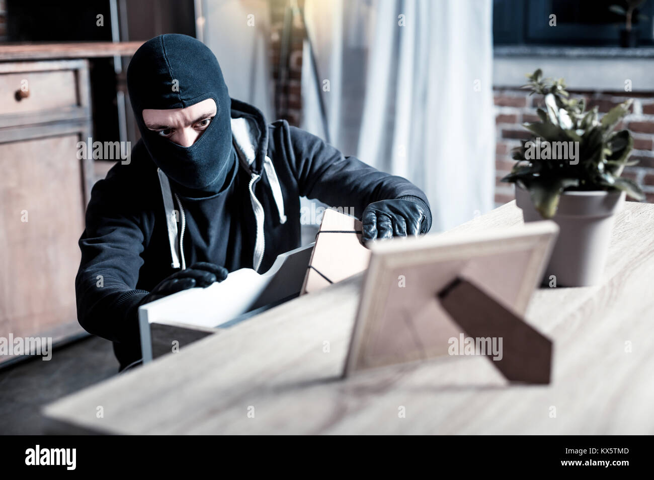 Masked thief stealing money from the table - Stock Image