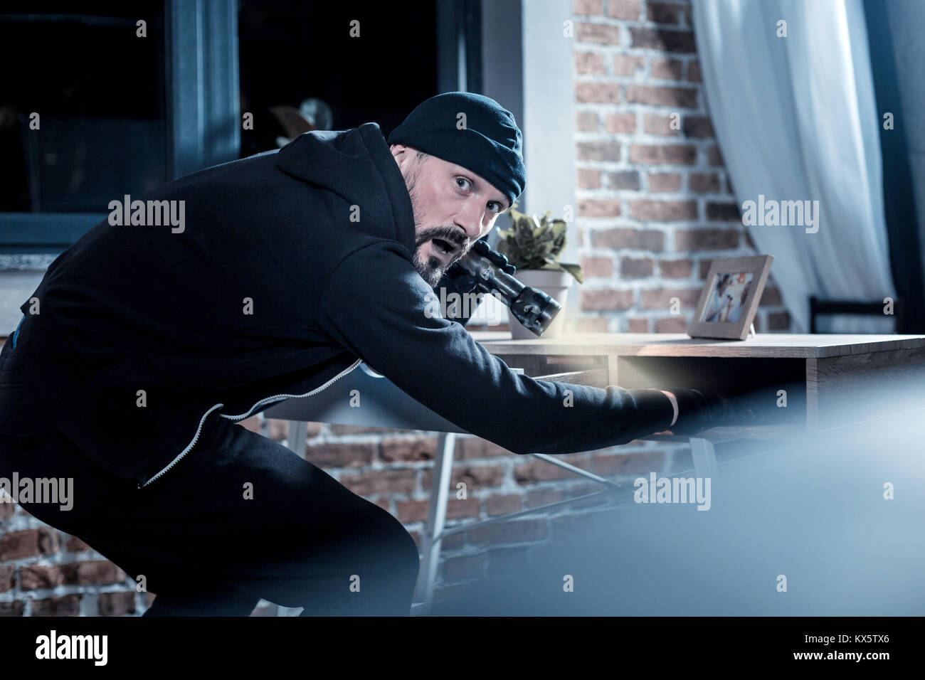 Nervous burglar looking for documents in the table - Stock Image