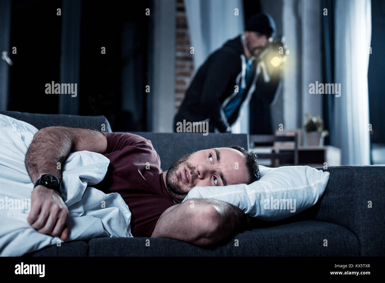 Alarmed man waking up and hearing someone being inside - Stock Image