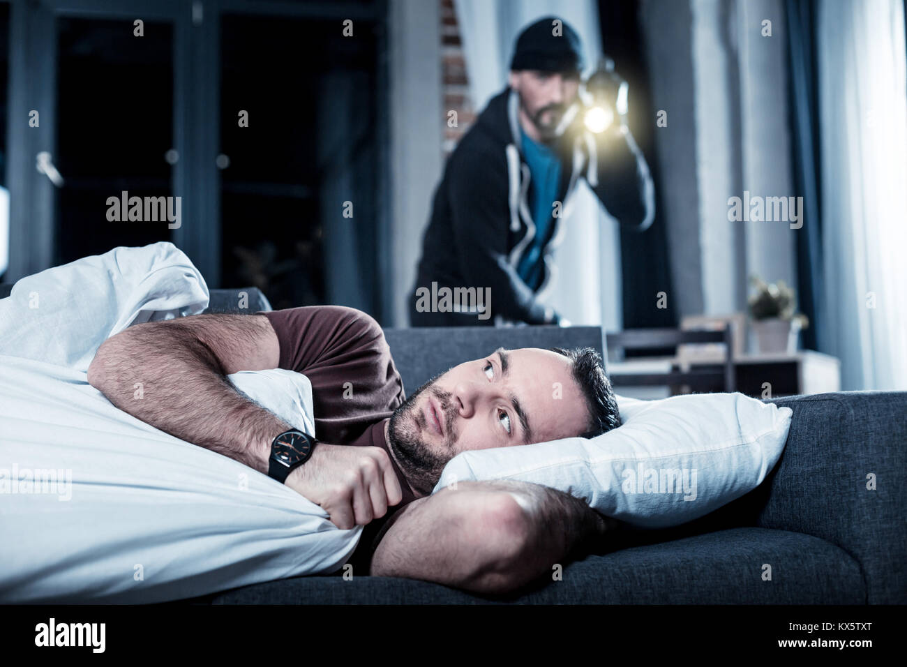 Agitated man waking up and hearing someone being inside - Stock Image