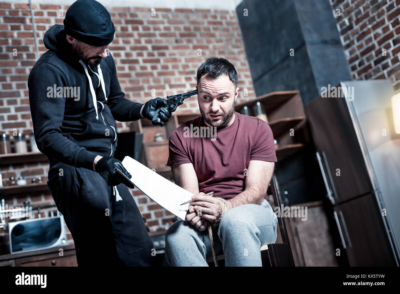 Irritated killer making the man sign a contract - Stock Image