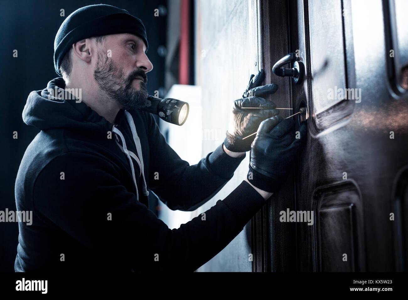 Professional robber unlocking the door - Stock Image