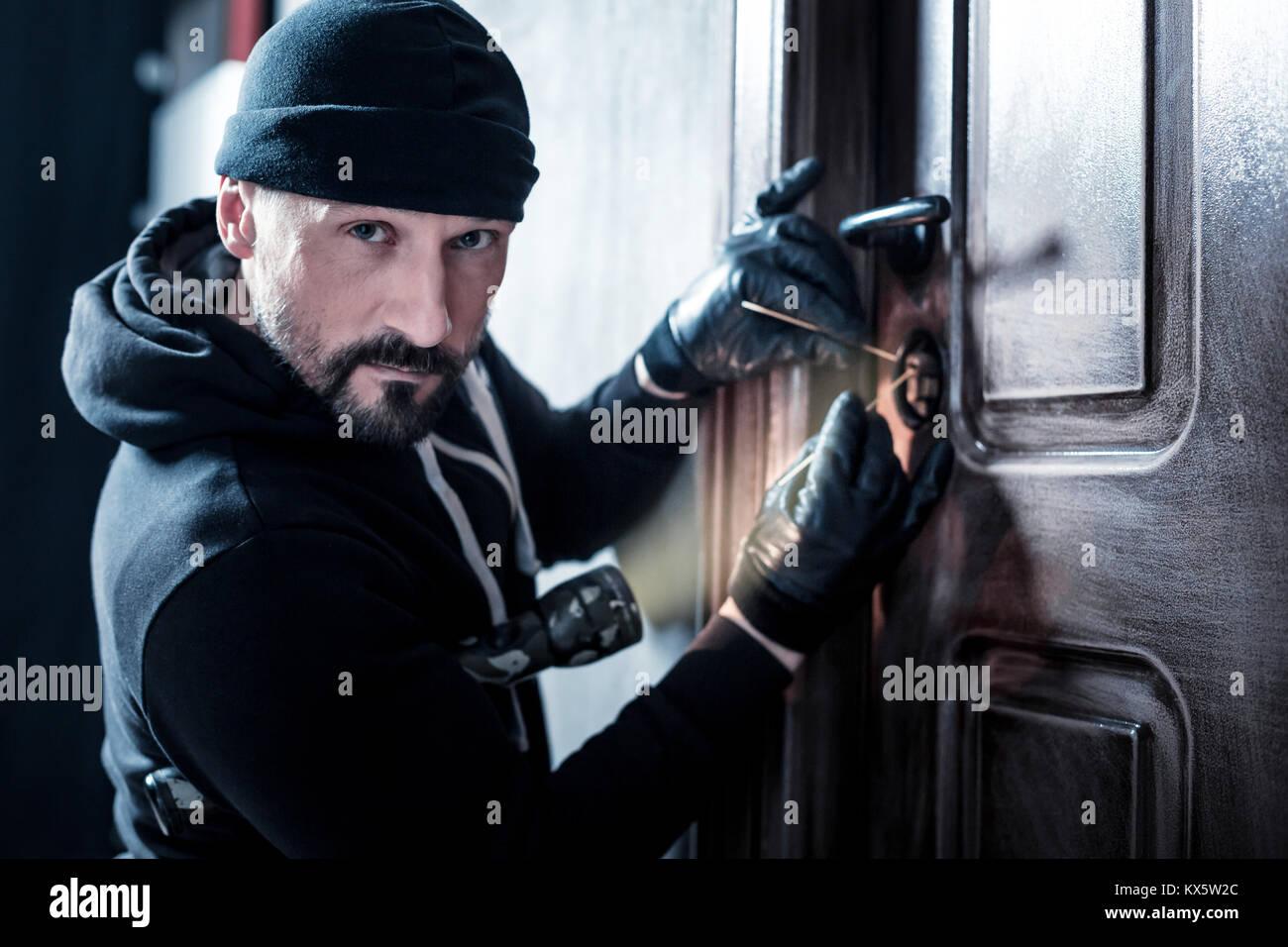 Skilful burglar unlocking the door - Stock Image