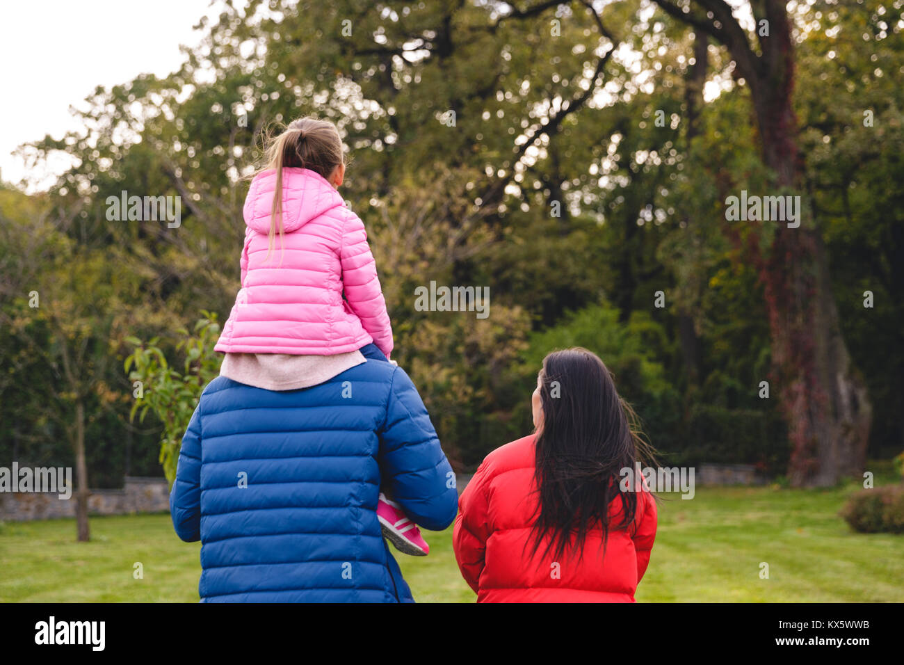 Back view of a young family spending time together outdoors, dad giving his daughter a piggyback ride - Stock Image