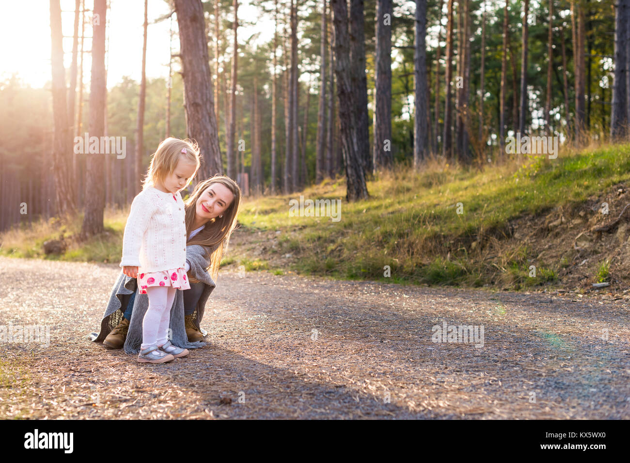 Happy young single mother taking a walk in a park with her toddler daughter. Family smiling and having fun outdoors. - Stock Image