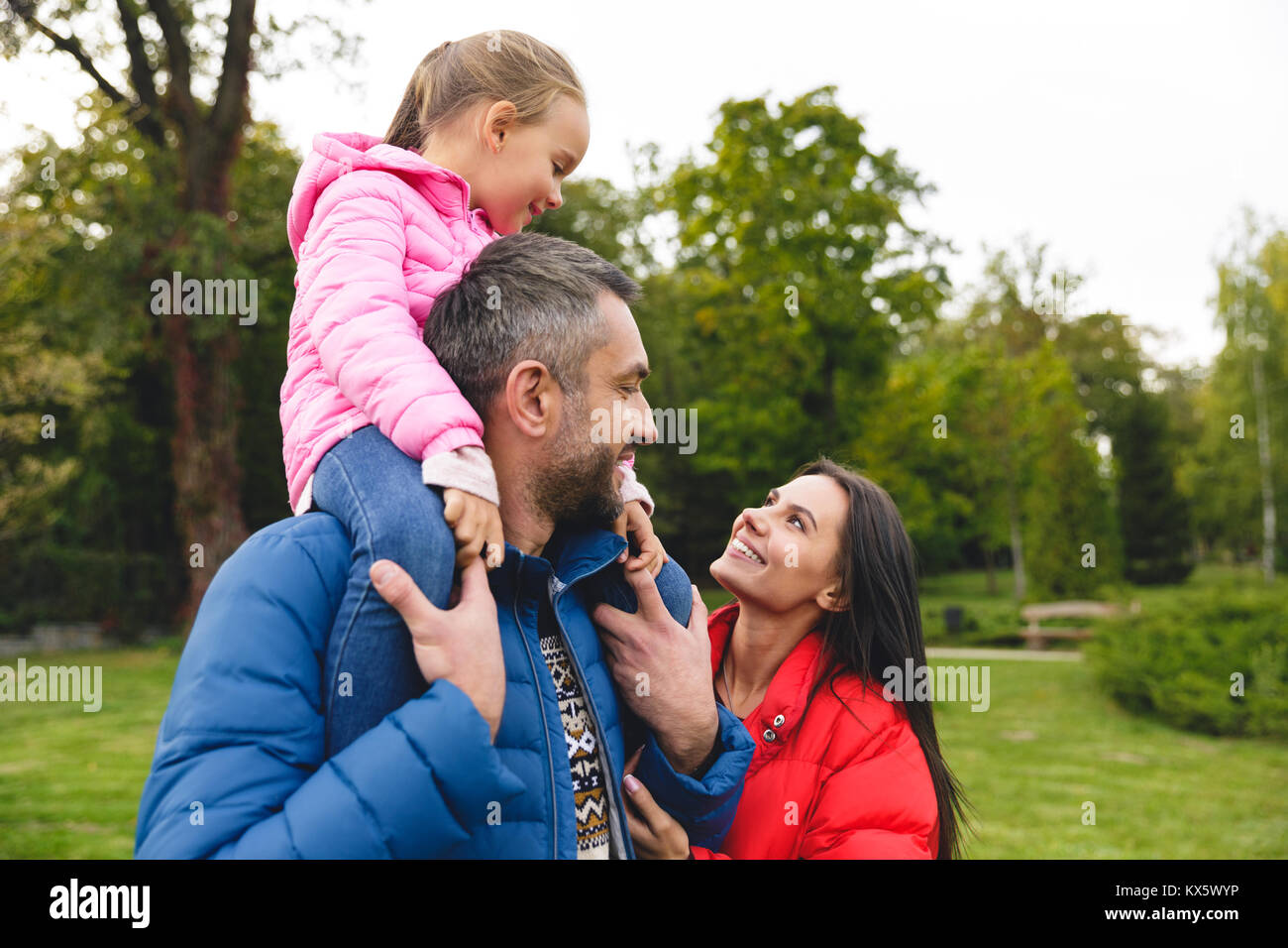 Beautiful young family spending time together outdoors, dad giving his daughter a piggyback ride - Stock Image