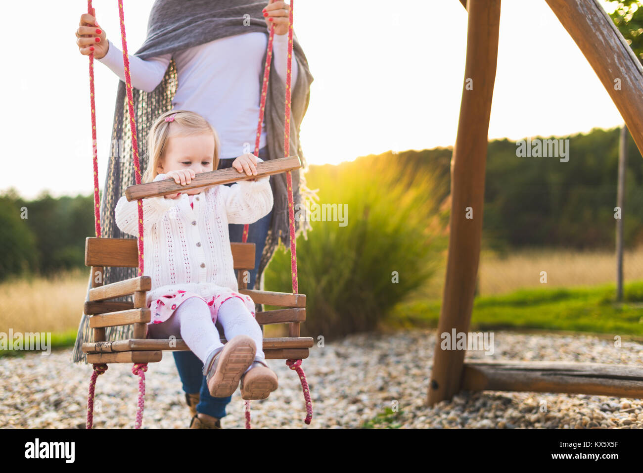 Single mother with toddler daughter swinging on a playground. Childhood, Family, Happy, Summer Outdoor Concept. - Stock Image