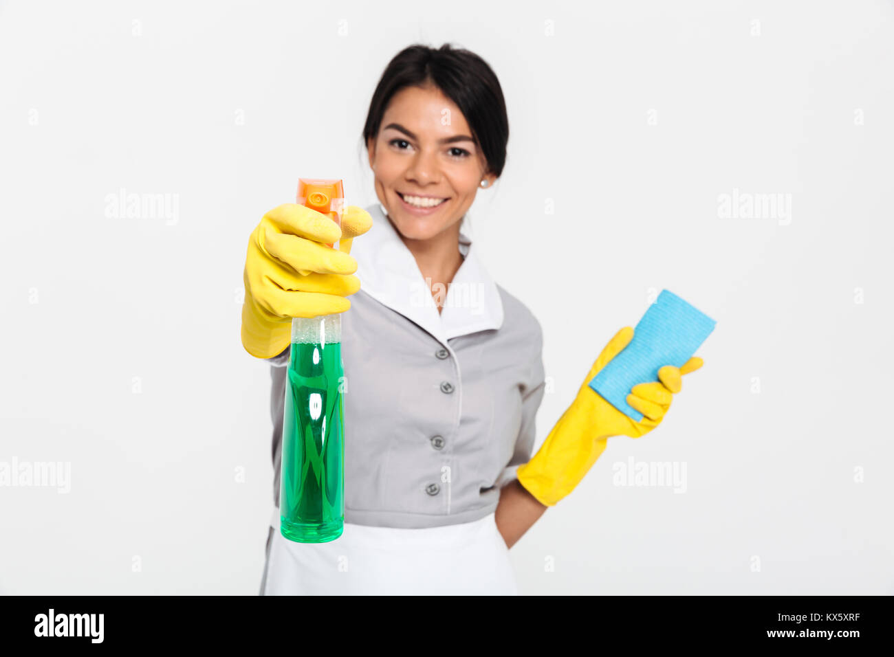 Close-up portrait of professional housekeeper in uniform and yellow rubber gloves spraying the cleaner on you, isolated Stock Photo