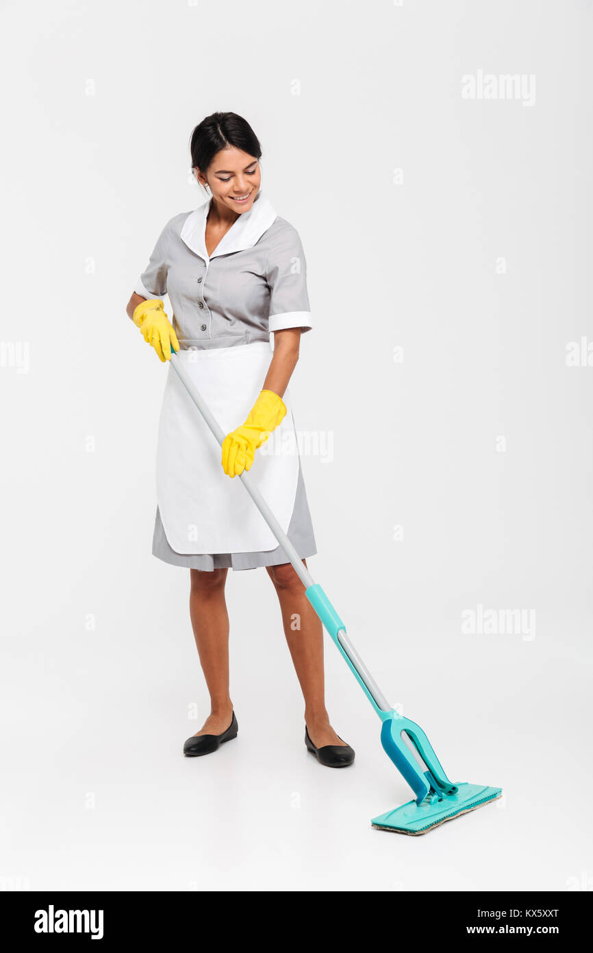 Full length photo of happy housekeeper in uniform cleaning floor with mop, isolated on white background Stock Photo