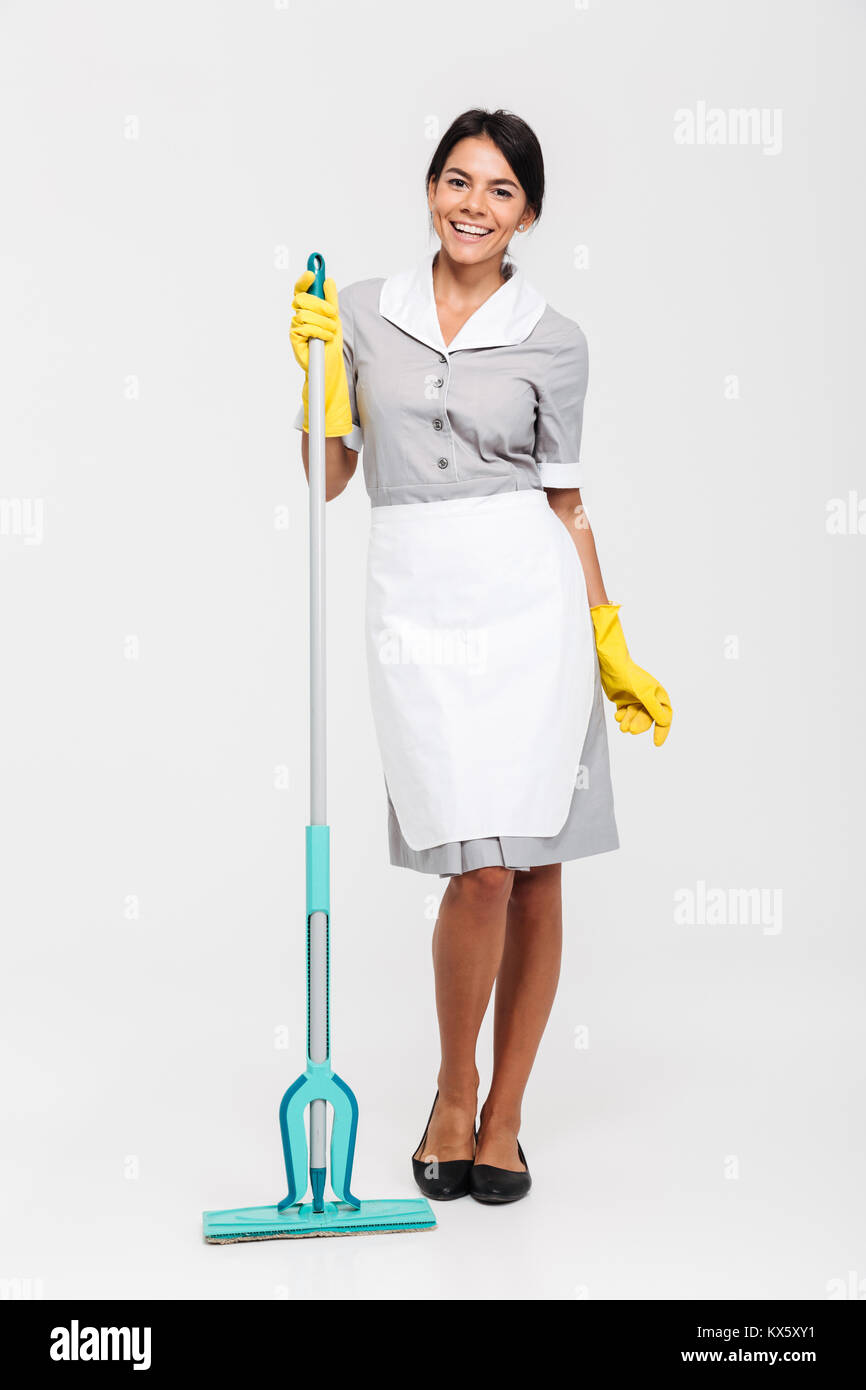 4901bb6c748 Full length portrait of cheerful brunette girl in uniform and rubber gloves  standing and holding mop, isolated on white background