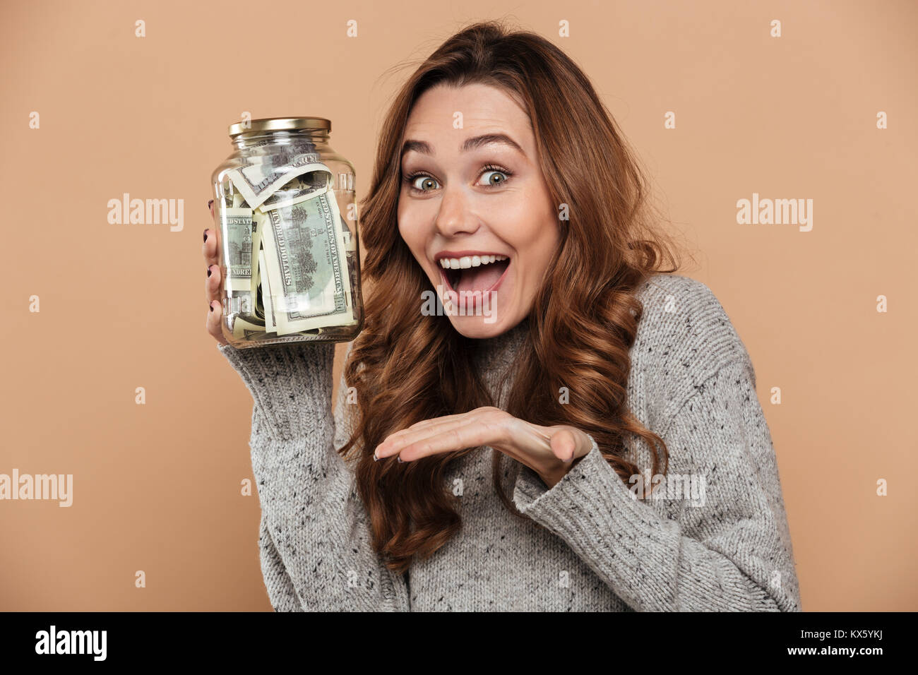 Happy brunette girl in gray jersey holding bank with dollar cash, looking at camera, isolated over beige background - Stock Image