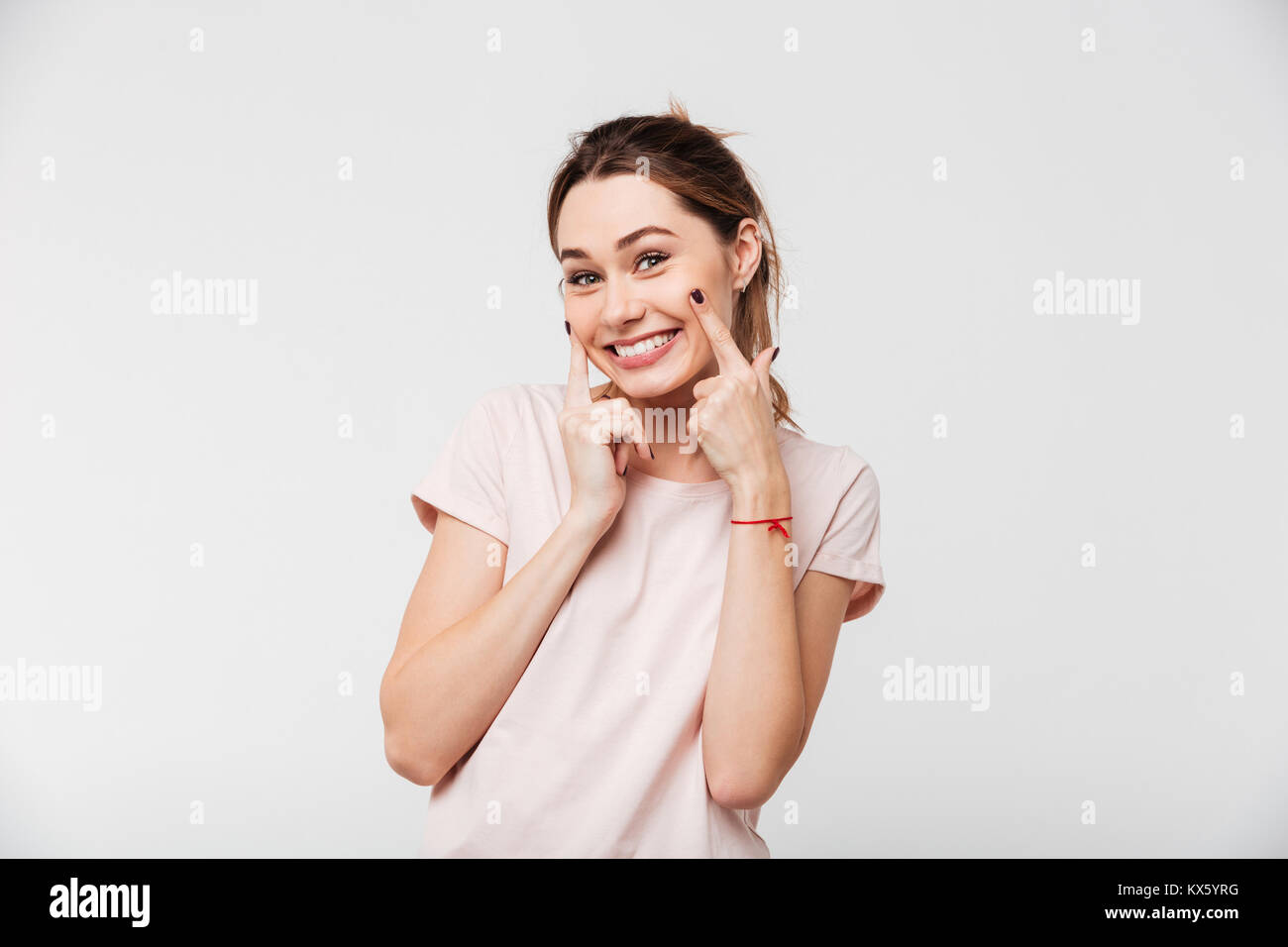 Portrait of a smiling cheerful girl grimacing and looking at camera isolated over white background - Stock Image