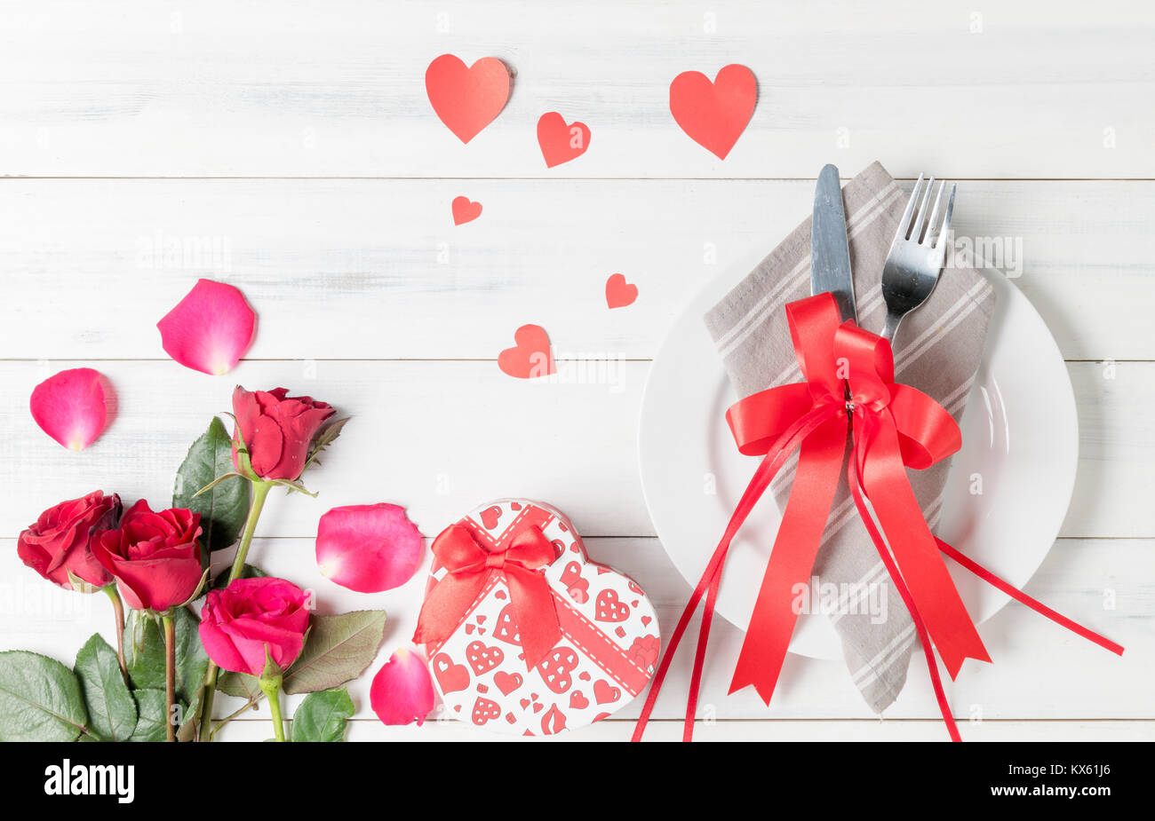 Valentine\'s day table setting with plate, fork, knife, red hearts ...
