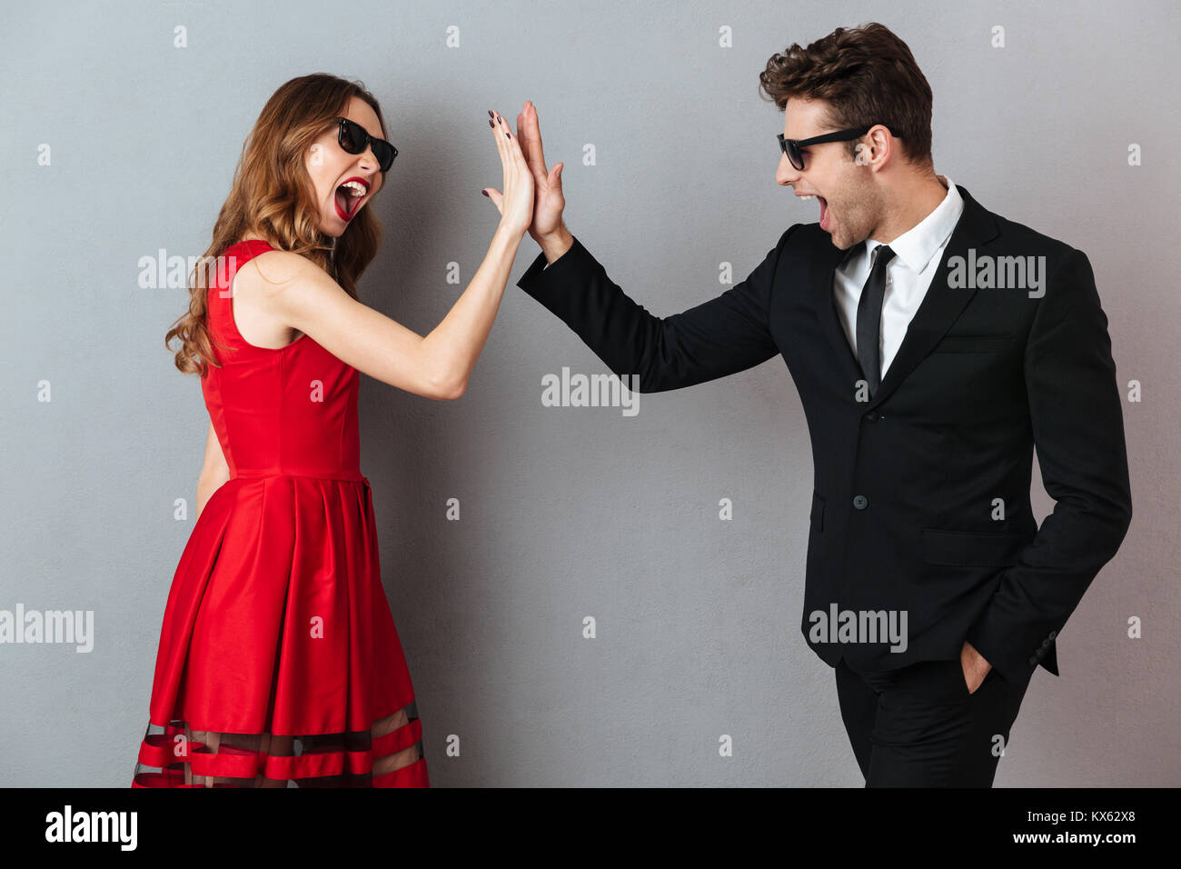 Portrait of a cheerful young couple dressed in formal wear and sunglasses standing and giving high five over gray - Stock Image
