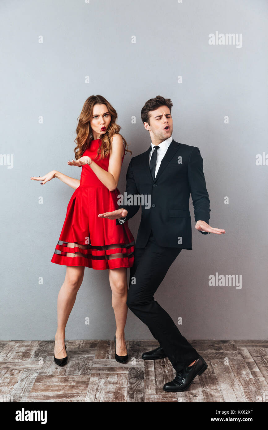 Full length portrait of an attractive happy couple dressed in formal wear dancing together and having fun over gray Stock Photo