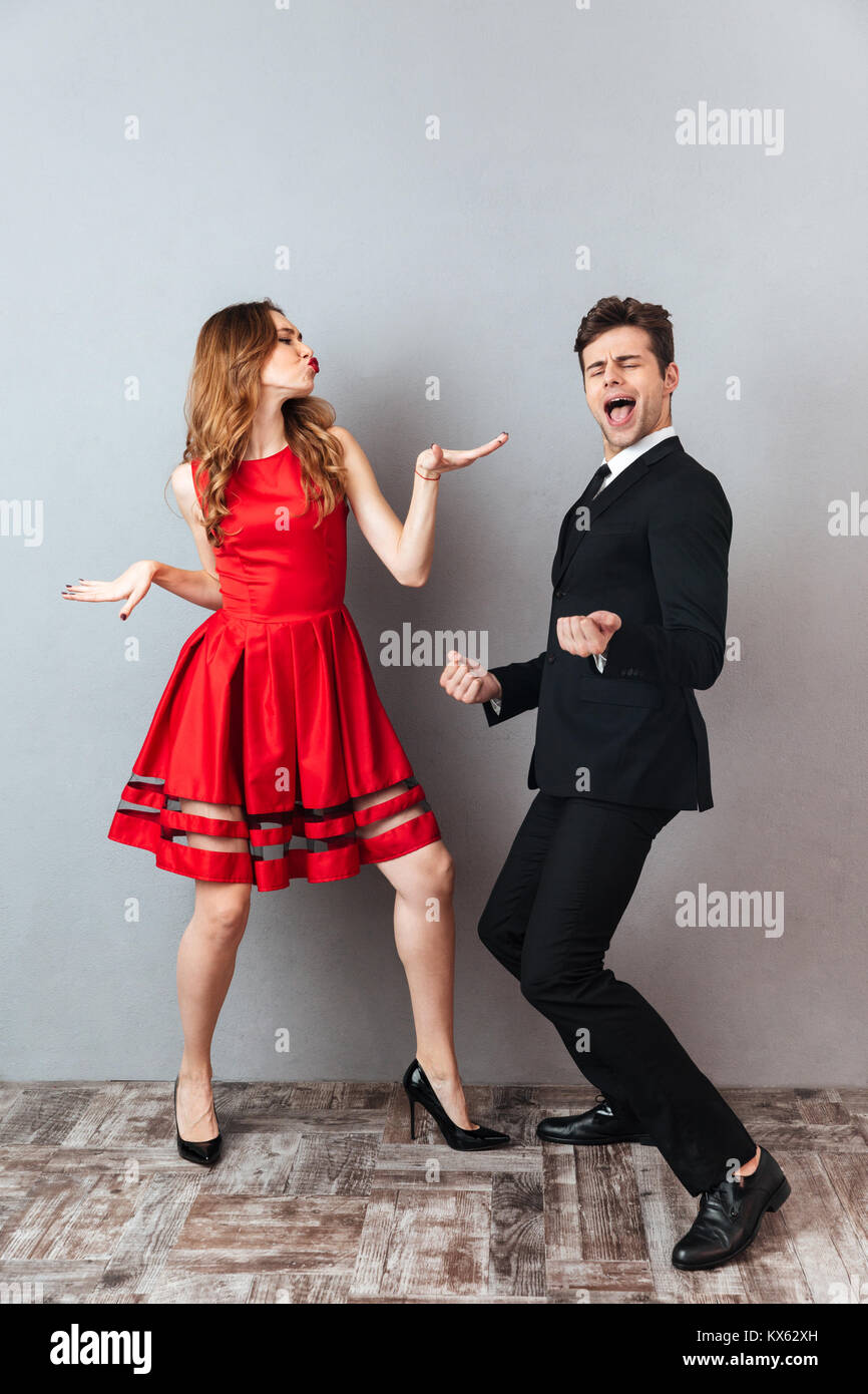 Full length portrait of a happy cheery couple dressed in formal wear dancing together and having fun over gray wall - Stock Image