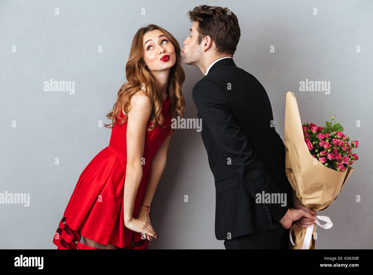 Portrait of a young lovely couple kissing while standing and holding flower bouquet over gray wall background - Stock Image