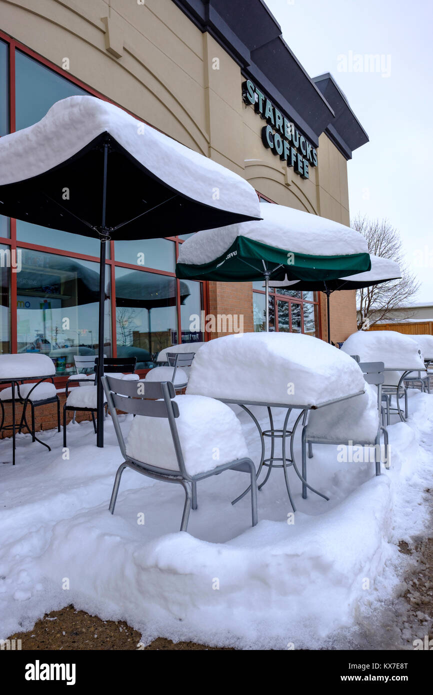 Empty starbucks coffee sidewalk patio tables chairs and umbrellas covered by fresh snow winter scene london ontario canada