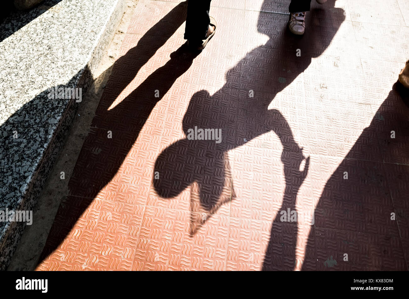 shadow of a 10-12 years old baby girl walking holding her mother's hand in the street of Kathmandu - Stock Image