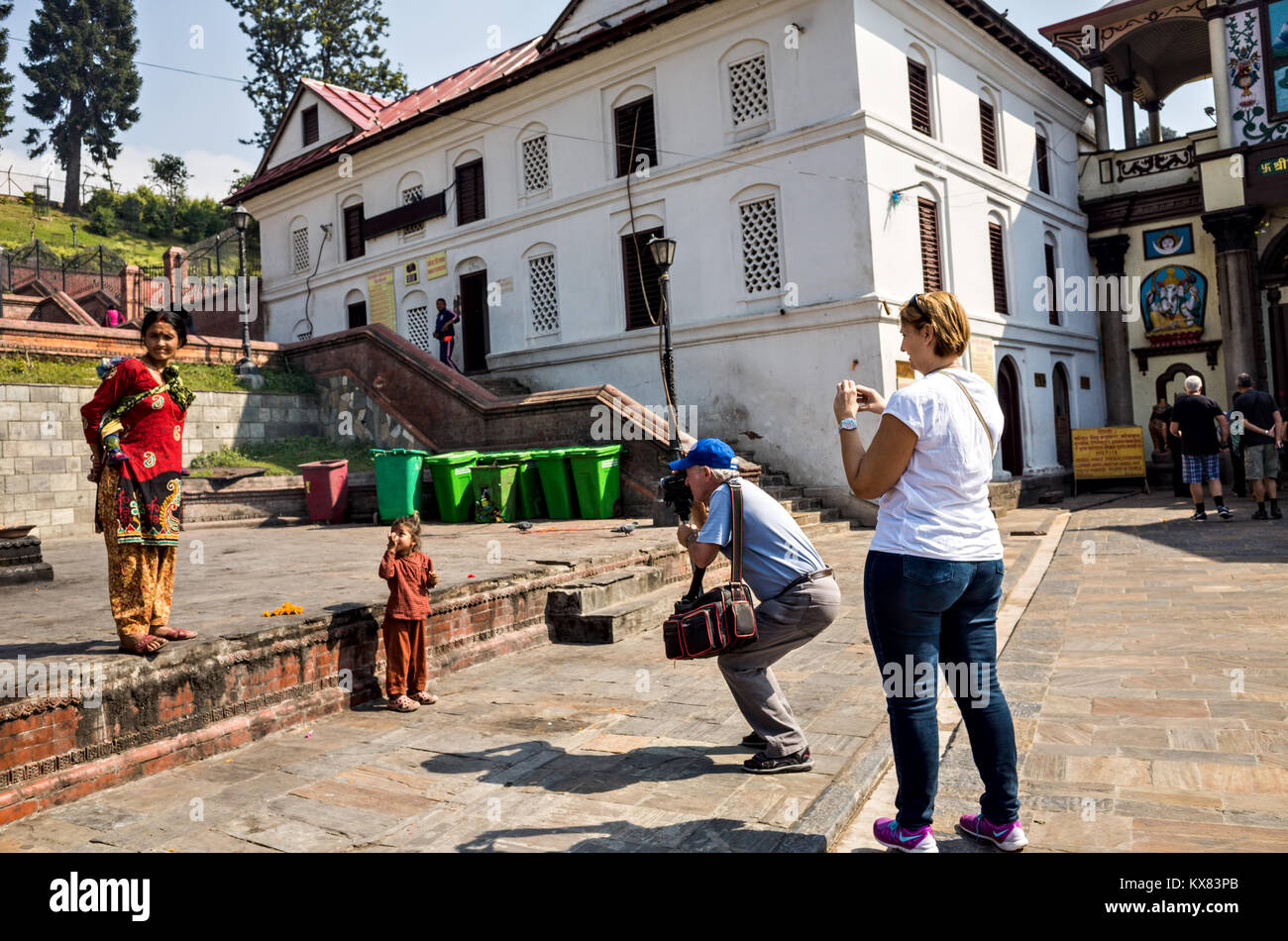 two western tourists photographers photographing a 8-10 years old child and his mother at Pashupatinath temple complex, - Stock Image