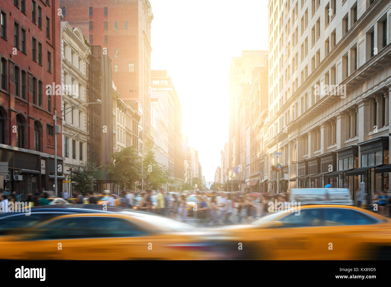 Fast paced motion in New York City as yellow taxi cabs speed down 5th Avenue with crowds of busy people walking - Stock Image